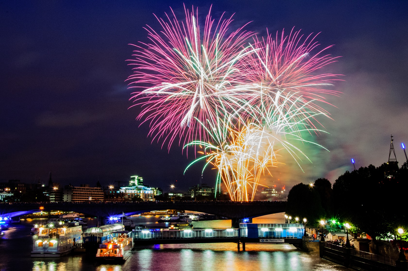 Firework display over the river Thames, with bridges and London skyline in the background