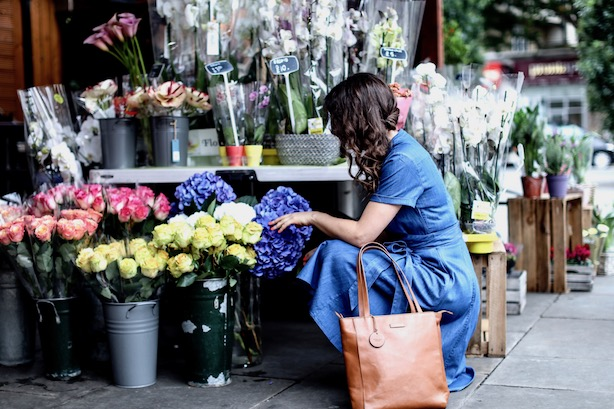 A woman selects flowers in kiosk