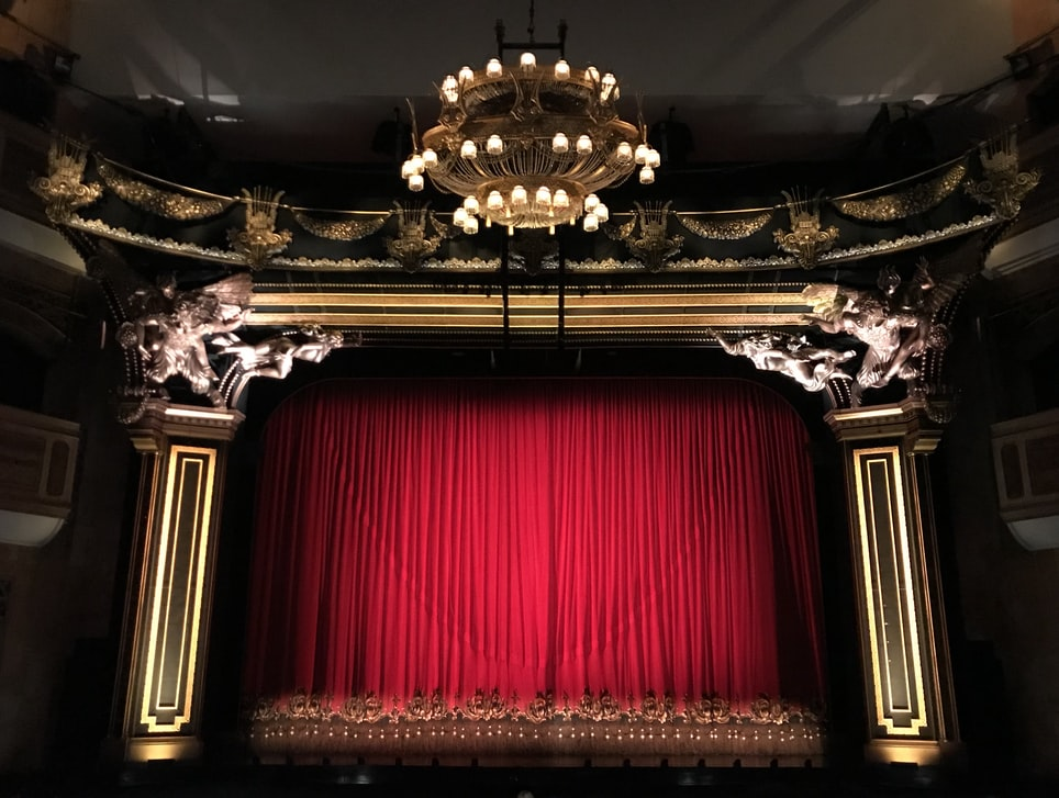 A theatre stage with curtain down
